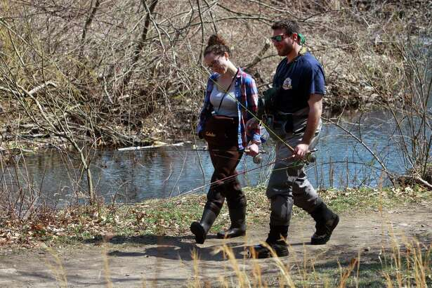 Lauren Sordellini and Gordon Kempler, both of Stamford, take a break to go have lunch during opening day of fishing season at Mill River in Fairfield, Conn., on Saturday Apr. 14, 2018.