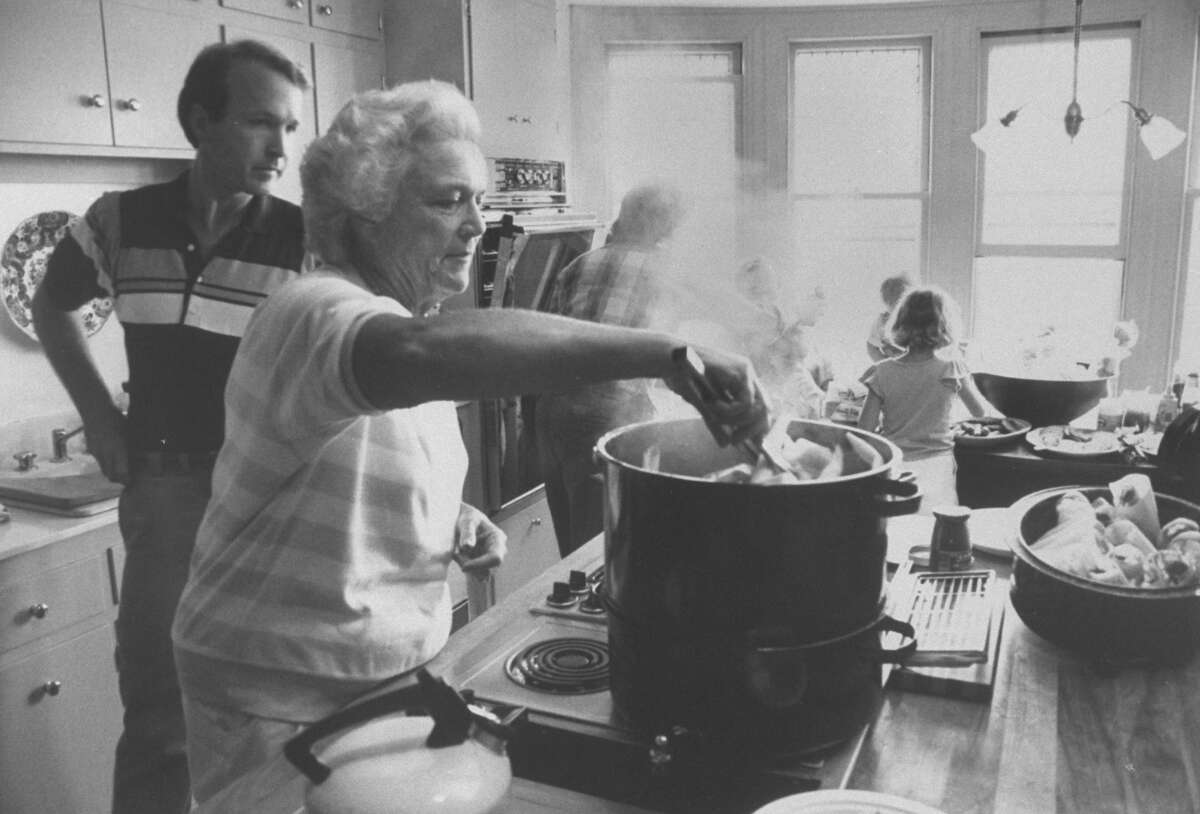 Neil Bush watching his mother, First Lady Barbara Bush, as she cooks.