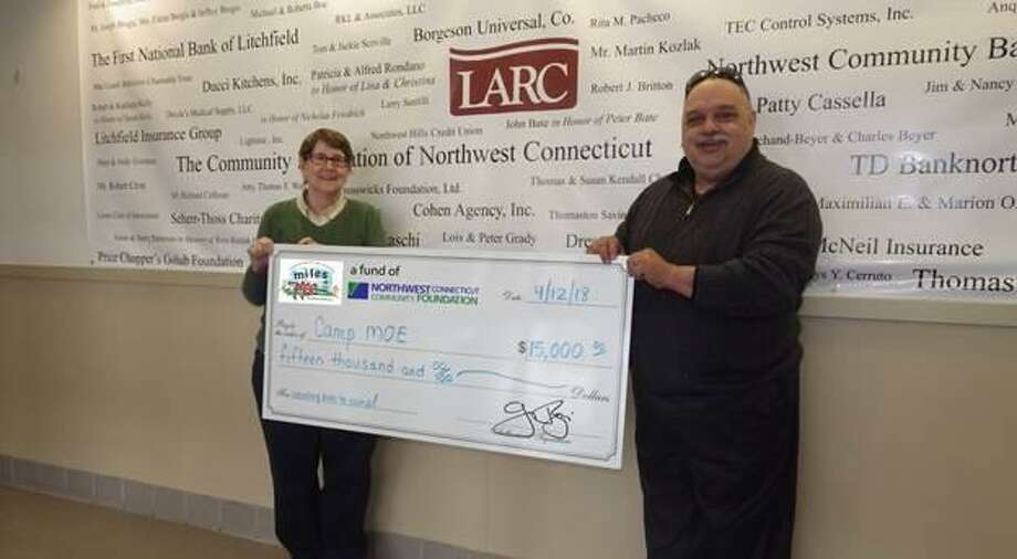 Katherine Marchand-Beyer and Emil Renzullo present a $15,000 donation from the Miles for Moe Fund of the Northwest Connecticut Community Foundation. The money will provide camperships for local children. Photo: Contributed Photo / Northwest Connecticut Community Foundation