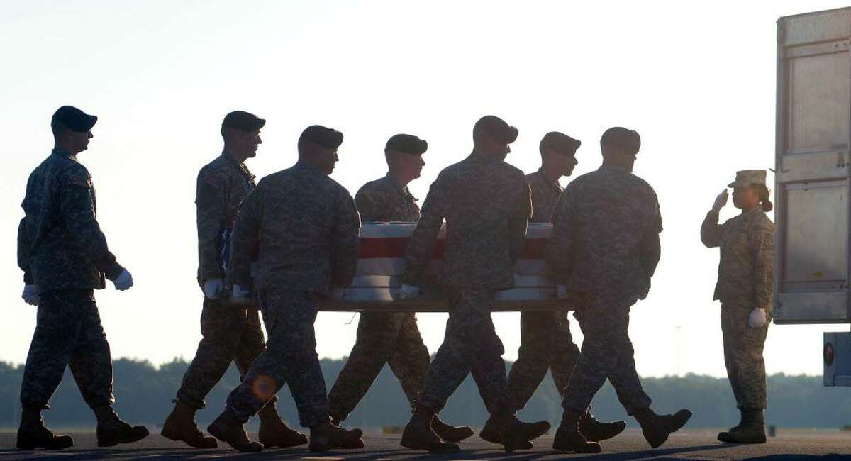 An Army team carries a transfer case containing the remains of Spc. Benjamin D. Osborn on Friday at Dover Air Force Base, Del. (Steve Ruark / Associated Press)