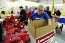 Americares employee Kristin Norley loads assembled first aid kits into a large box inside the Americares headquarters on Hamilton Ave. in Stamford, Conn. on Wednesday, April 18, 2018. Volunteers gathered at Americares to help create 1,500 first aid kits which contain essential first aid items such as bandages and burn gel.