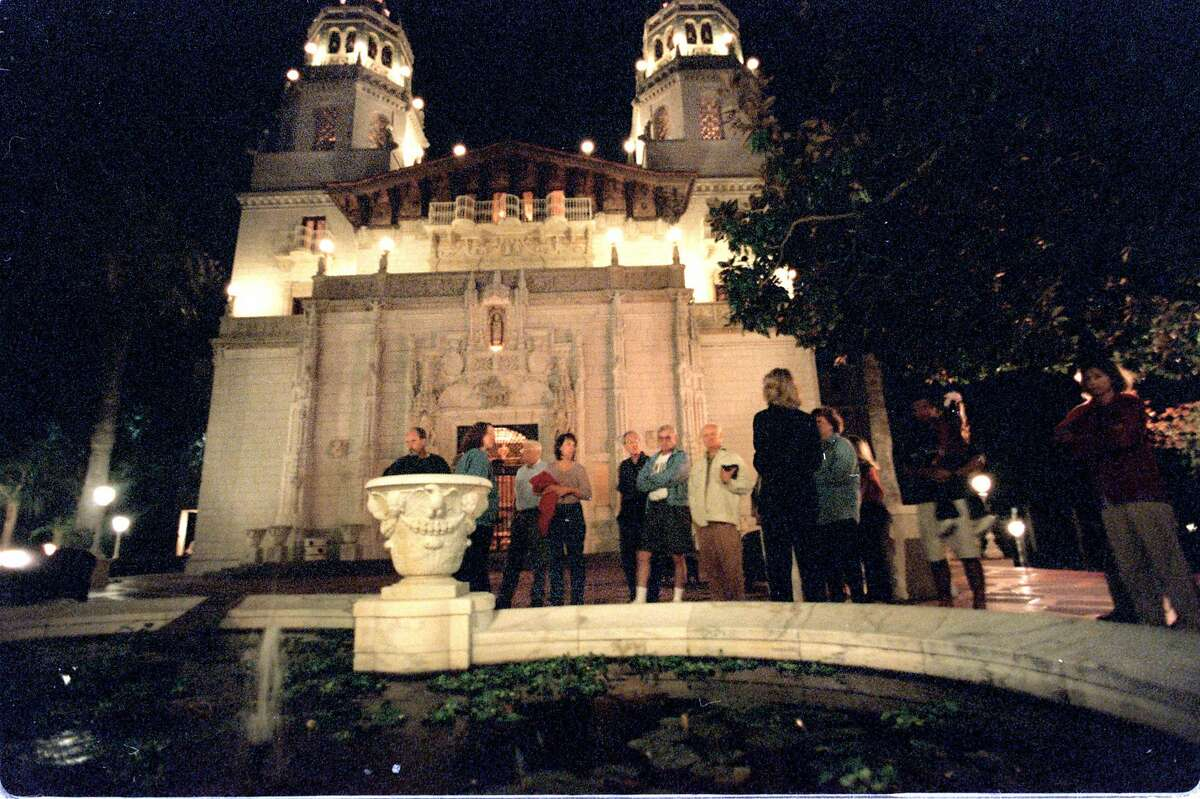 Tourists listen to a guide outside the main house at Hearst Castle during an evening tour last fall. the Castle is open Friday and Saturday evenings during the spring and fall.