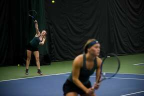 Dow senior Kelly Livingston serves the ball during her #1 doubles match with her partner, senior Tatum Matthews, against a Birmingham Seaholm pair on Wednesday, April 18, 2018 at the Greater Midland Tennis Center. (Katy Kildee/kkildee@mdn.net)