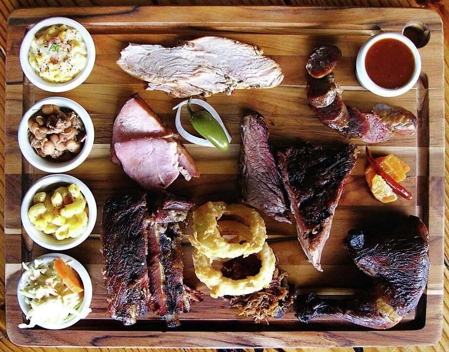 Barbecue and sides from Blanco BBQ. Clockwise from top left: creamed corn, turkey, sausage, barbecue sauce, carrot escabeche, chicken, pulled pork, onion rings, pork ribs, cole slaw, mac and cheese, Blanco beans, ham and brisket. Photo: Mike Sutter /San Antonio Express-News