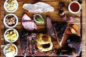 Barbecue and sides from Blanco BBQ. Clockwise from top left: creamed corn, turkey, sausage, barbecue sauce, carrot escabeche, chicken, pulled pork, onion rings, pork ribs, cole slaw, mac and cheese, Blanco beans, ham and brisket.