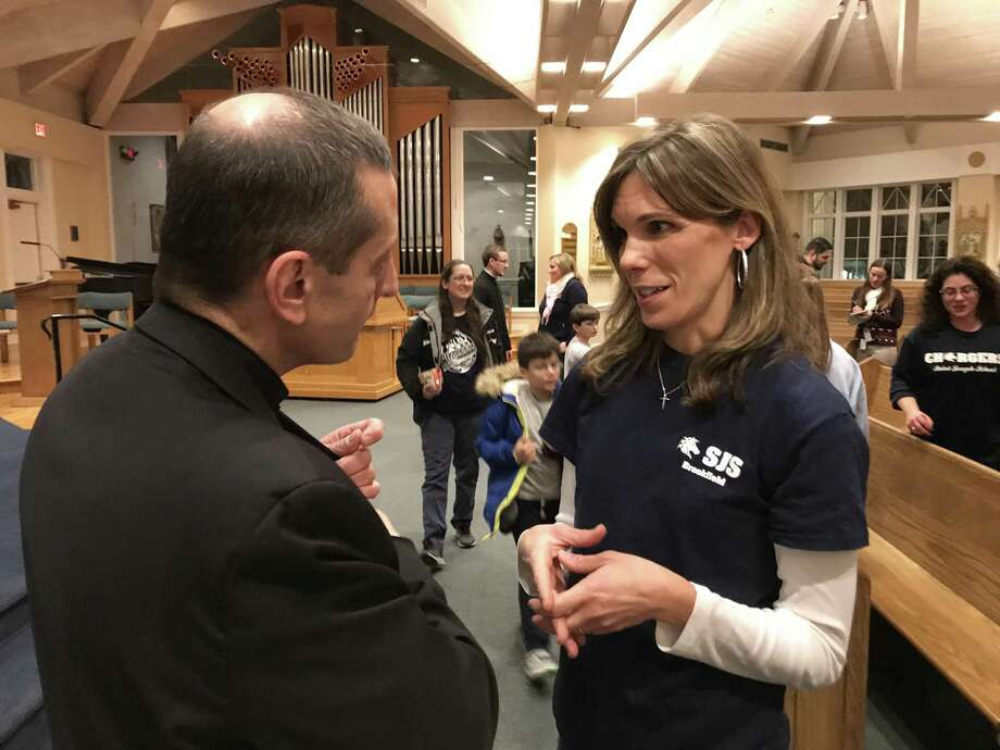Bishop Frank Caggiano speaks with Jen Conlon, who is on the Home School Association at St. Joseph's School in Brookfield. Caggiano has proposed changing the educational model at St. Joseph's. Caggiano and Steve Cheeseman, superintendent of the Diocese of Bridgeport Catholic schools, made the announcement at the parish Thursday night, January 18, 2018. Photo: Contributed Photo/ Diocese Of Bridgeport / Hearst Connecticut Media / The News-Times Contributed