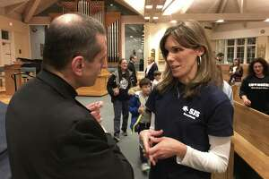 Bishop Frank Caggiano speaks with Jen Conlon, who is on the Home School Association at St. Joseph's School in Brookfield. Caggiano has proposed changing the educational model at St. Joseph's. Caggiano and Steve Cheeseman, superintendent of the Diocese of Bridgeport Catholic schools, made the announcement at the parish Thursday night, January 18, 2018.