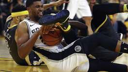 San Antonio Spurs' Rudy Gay hangs on to the ball as Golden State Warriors' Draymond Green rolls over him during the second half in Game 2 of a first-round NBA basketball playoff series, Monday, April 16, 2018, in Oakland, Calif. Golden State won 116-101. (AP Photo/Ben Margot)