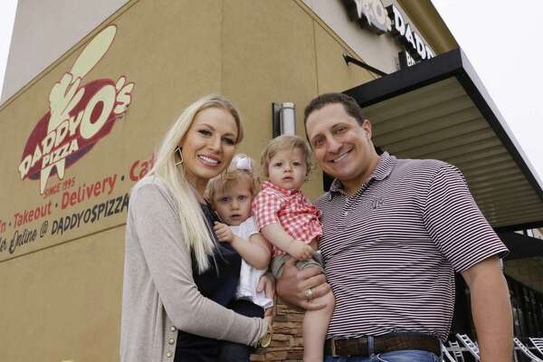 The Koch family, from left, Jacque; Claire, age 2; J.W., age 1; and David outside DaddyO's Pizza Parlor, where they happened upon three elderly women whom they assisted and took back to their home during hurricane Harvey last year.