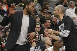 San Antonio Spurs star Kawhi Leonard (left), who sat on the bench most of the season because of an injury, discusses a play with guard Tony Parker during a game in February. A reader has some questions for  Leonard.