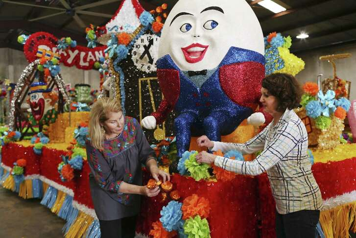 "Battle of Flowers parade committee members Lynn Ziegler, left, and Janet Putman work on the Playland Park float at a warehouse on Stafford Street near Fort Sam Houston, Wednesday, April 18, 2018. This float is part of the public school floats with this year's theme, ""Treasured Pleasures."" The nine floats feature iconic San Antonio scene such as the Brackenridge Park, miniature golf and the movie drive-in. Each floats features students from San Antonio area high schools."