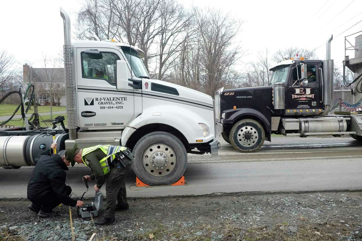 Environmental engineer, Gary McPherson, left, with the New York State Department of Environmental Conservation, and NYSDEC Police Officer, Brian Canzeri, set up equipment to perform an emissions test on a truck at a checkpoint outside the Dunn construction and demolition debris landfill on Wednesday, April 18, 2018, in Rensselaer, N.Y. (Paul Buckowski/Times Union)