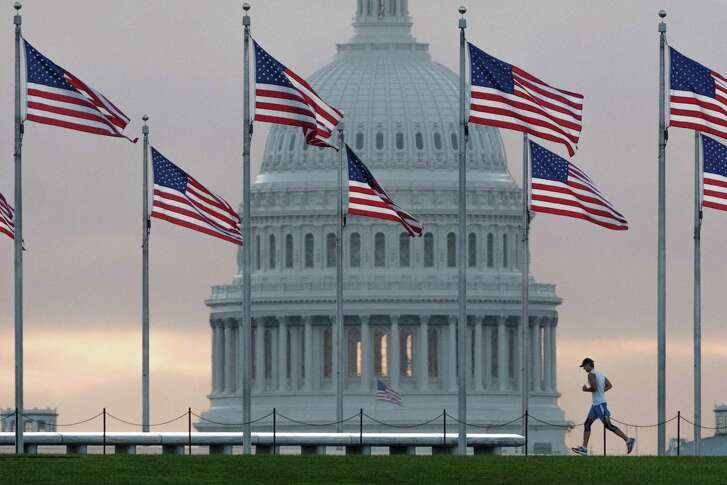 An early morning runner in 2017 crosses in front of the U.S. Capitol as he passes the flags circling the Washington Monument in Washington.
