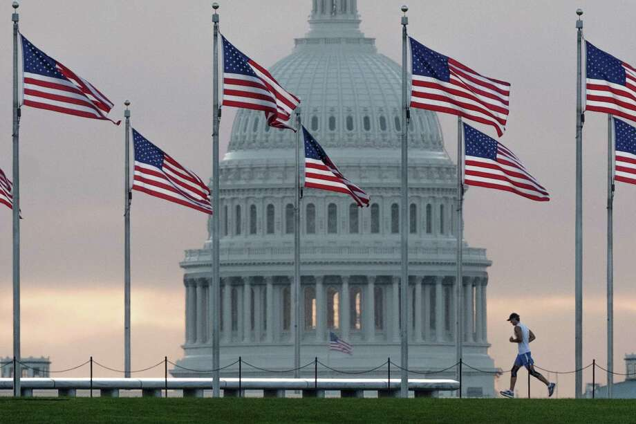 An early morning runner in 2017 crosses in front of the U.S. Capitol as he passes the flags circling the Washington Monument in Washington. Photo: J. David Ake, STF / Associated Press / Copyright 2017 The Associated Press. All rights reserved.