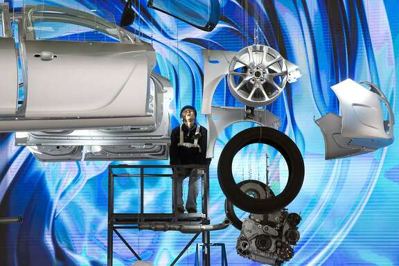 FILE - In this April 18, 2015, file photo,  a worker prepares a display ahead of the Auto Shanghai show, to be held at the National Exhibition and Convention Center in Shanghai.  Chinese exporters of goods from electronics to motorcycle parts are scrambling to insulate themselves from U.S. President Donald Trump�s proposed tariff hike. They are weighing plans to rush shipments to American customers ahead of the increase, raise prices or find other markets. Some are looking at shipping goods through other countries to hide their Chinese origin. (AP Photo/Ng Han Guan, File)