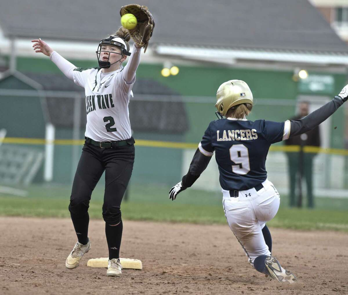New Milford's Sara Mickelson (2) reaches for the throw as Notre Dame's Lucy Grant slides safely into second for the steal Wednesday afternoon at New Milford High School.