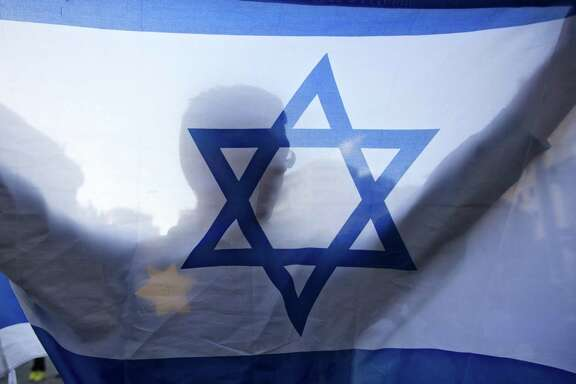 In this July 14, 2014 photo, a right-wing Israeli holds a flag and wears a Star of David patch resembling the one Jews were forced to wear in Nazi Germany, during a demonstration in Jerusalem. As Israel marks the 70th anniversary of statehood starting at sundown Wednesday, satisfaction over its successes and accomplishments share the stage with a grim disquiet over the never-ending conflict with the Palestinians, internal divisions and an uncertain place in a hostile region.