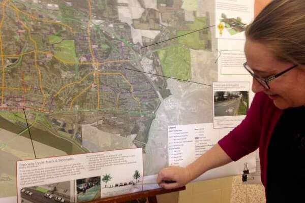 "President Mary Vandevord of HeartLands Conservancy explains elements in a legend on a satellite map of proposed improvements in the draft, 20-year, Alton ""Pedestrian and Bicycle Master Plan"" during an open house Tuesday at Alton City Hall."