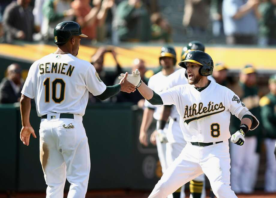 OAKLAND, CA - APRIL 18:  Jed Lowrie #8 of the Oakland Athletics is congratulated by Marcus Semien #10 after he hit a two-run home run to give the Athletics a 11-10 lead in the eighth inning against the Chicago White Sox at Oakland Alameda Coliseum on April 18, 2018 in Oakland, California.  (Photo by Ezra Shaw/Getty Images) Photo: Ezra Shaw / Getty Images