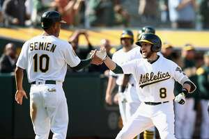 OAKLAND, CA - APRIL 18:  Jed Lowrie #8 of the Oakland Athletics is congratulated by Marcus Semien #10 after he hit a two-run home run to give the Athletics a 11-10 lead in the eighth inning against the Chicago White Sox at Oakland Alameda Coliseum on April 18, 2018 in Oakland, California.  (Photo by Ezra Shaw/Getty Images)