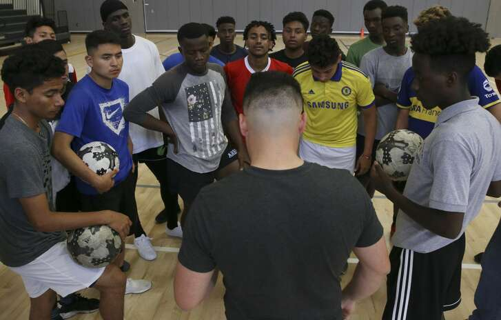 Wisdom High School boys soccer team gather tgether around coach Fidel Andrade before practice in the school gym on Wednesday, April 18, 2018, in Houston. The team pracices in the gym because they don't have a field and they are advancing to state tournament. ( Yi-Chin Lee / Houston Chronicle )