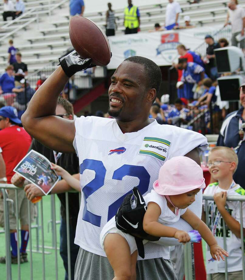 Buffalo Bills running back Fred Jackson (22) holds his daughter, Maecen, as he tosses the ball to his son following a practice at their NFL football training camp in Pittsford, N.Y., Monday, July 21, 2014. (AP Photo/Bill Wippert) ORG XMIT: NYBW04 Photo: Bill Wippert / FR170745 AP