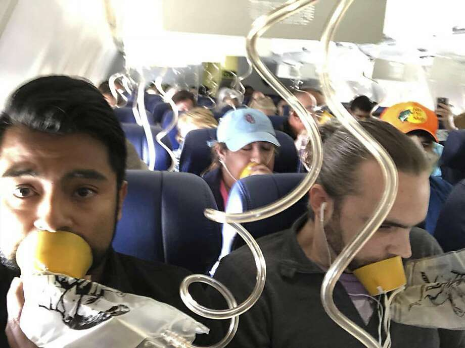 In this April 17, 2018 photo provided by Marty Martinez, Martinez, left, appears with other passengers after a jet engine blew out on the Southwest Airlines Boeing 737 plane he was flying in from New York to Dallas, resulting in the death of a woman who was nearly sucked from a window during the flight with 149 people aboard. (Marty Martinez via AP) Photo: Marty Martinez, Associated Press