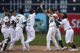 Oakland Athletics' Matt Olson (28) is congratulated by teammates, including Marcus Semien (10) ,after driving in the winning run against the Chicago White Sox in the 14th inning of a baseball game Wednesday, April 18, 2018, in Oakland, Calif. (AP Photo/Ben Margot)