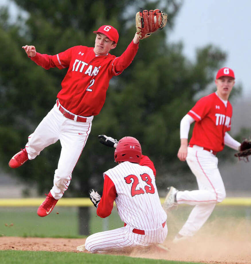 A Glenwood infielder jumps to catch the throw as Jacksonville's Jack Rohn steals second base during a baseball game in Jacksonville Wednesday afternoon. Photo:       Dennis Mathes | Journal-Courier