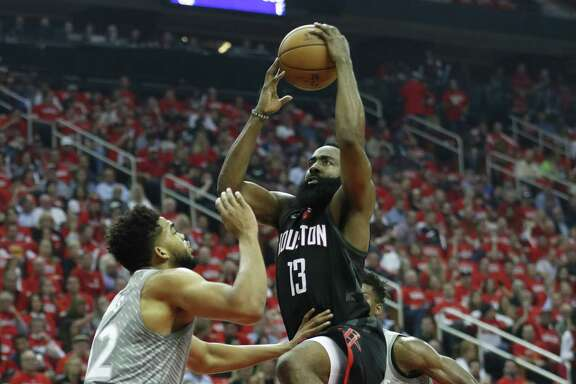 Rockets guard James Harden finds a path to the basket but is challenged by Timerwolves center Karl-Anthony Towns during the first half of Game 2 on Wednesday night.