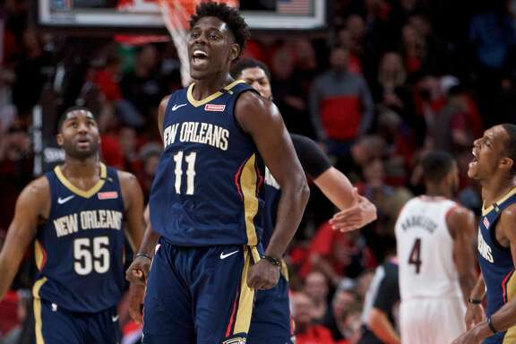New Orleans Pelicans guard Jrue Holiday, center, guard Rajon Rondo, right, and forward E'Twaun Moore, left, celebrate during the second half of Game 2 against the Portland Trail Blazers in an NBA basketball first-round playoff series Tuesday, April 17, 2018, in Portland, Ore. The Pelicans won 111-102. (AP Photo/Craig Mitchelldyer)