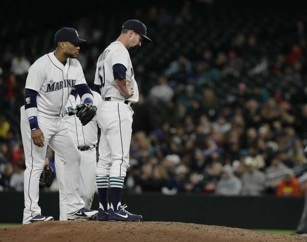 Seattle Mariners relief pitcher Nick Vincent, right, waits on the mound before he was pulled from the game as second baseman Robinson Cano stands behind him at left, during the seventh inning of a baseball game agains the Houston Astros on Wednesday, April 18, 2018, in Seattle. (AP Photo/Ted S. Warren)