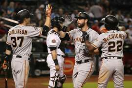 PHOENIX, AZ - APRIL 18:  Brandon Belt #9 of the San Francisco Giants high fives Kelby Tomlinson #37 and Andrew McCutchen #22 after hitting a two-run home run against the Arizona Diamondbacks during the 10th inning of the MLB game at Chase Field on April 18, 2018 in Phoenix, Arizona.  (Photo by Christian Petersen/Getty Images)