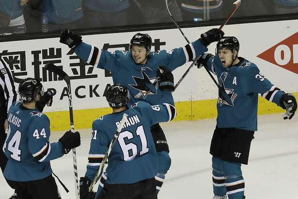 San Jose Sharks center Tomas Hertl, center, from the Czech Republic, celebrates with Marc-Edouard Vlasic (44), Justin Braun (61) and Logan Couture after scoring a goal against the Anaheim Ducks during the third period of Game 4 of an NHL hockey first-round playoff series in San Jose, Calif., Wednesday, April 18, 2018. The Sharks won 2-1 to sweep the series. (AP Photo/Jeff Chiu)
