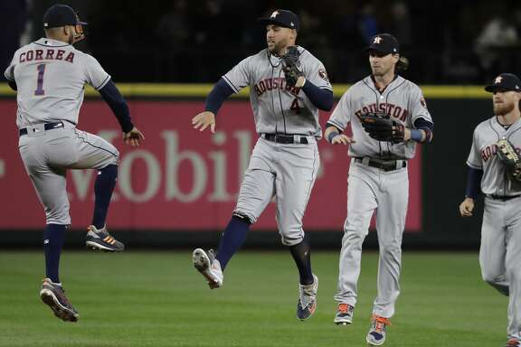Houston Astros' Carlos Correa, George Springer, Josh Reddick and Derek Fisher, from left, celebrate after the Astros defeated the Seattle Mariners 7-1 in a baseball game Wednesday, April 18, 2018, in Seattle. (AP Photo/Ted S. Warren)