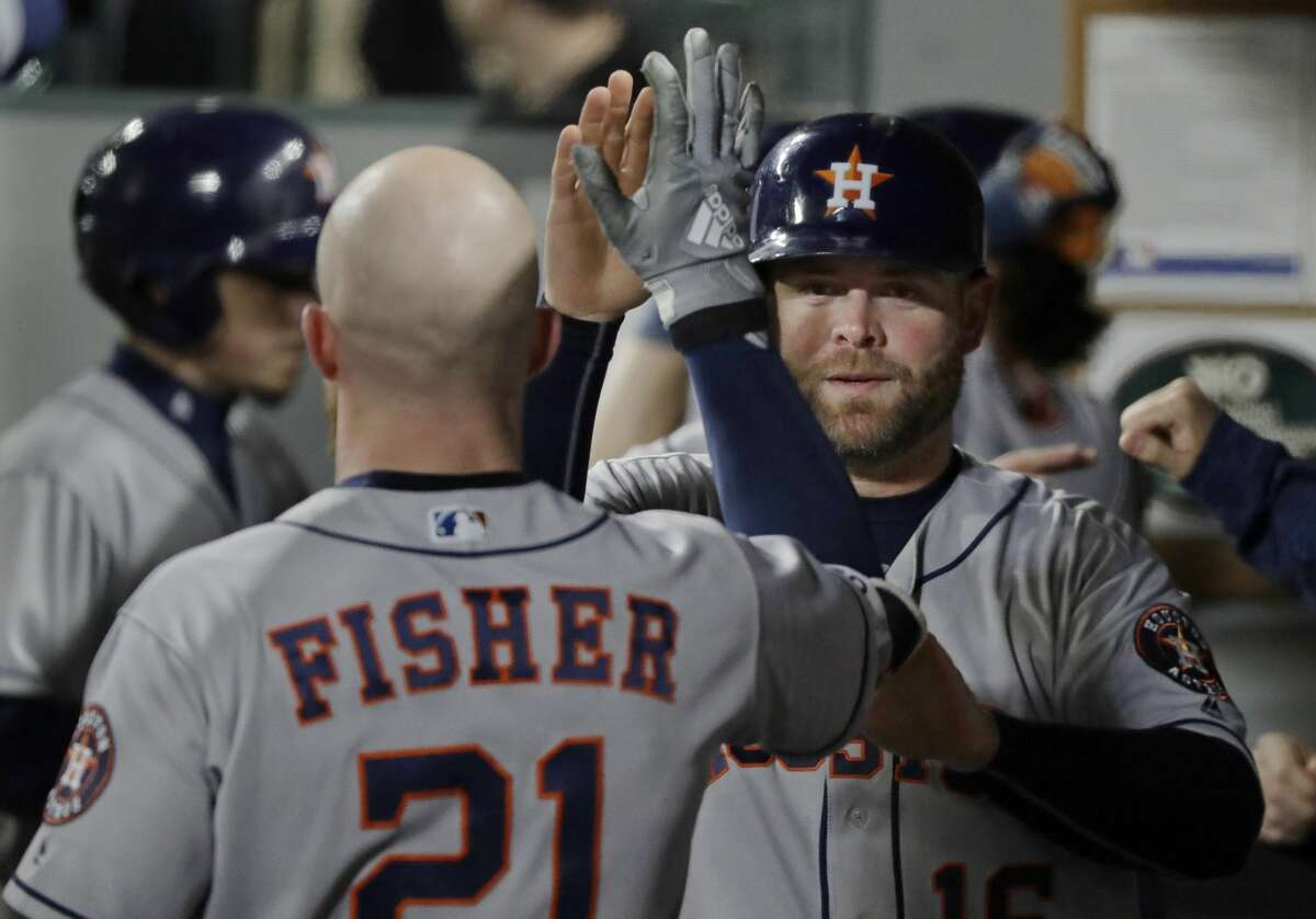 Houston Astros' Derek Fisher, left, greets Brian McCann in the dugout after McCann scored on a double by George Springer during the seventh inning of a baseball game against the Seattle Mariners, Wednesday, April 18, 2018, in Seattle. (AP Photo/Ted S. Warren)