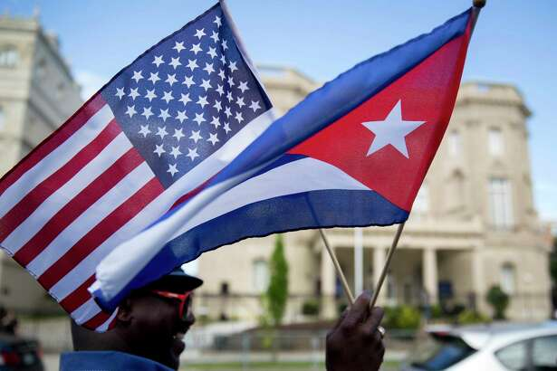 Eduardo Clark holds American and Cuban flags across the street from the Cuban embassy in Washington on July 20, 2015.