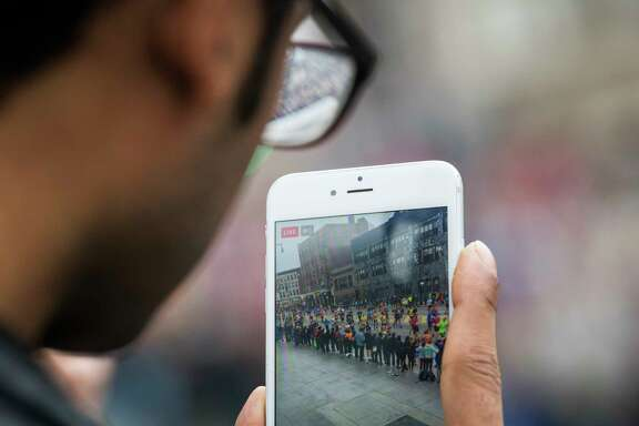 FILE -- A bystander records runners in the New York City marathon, in Brooklyn, Nov. 5, 2017. Not long ago, a filmmaker wouldn't dream of shooting a movie on a phone because the quality was so inferior to what you could capture on pricier devices. But that's changing. (Joshua Bright/The New York Times)