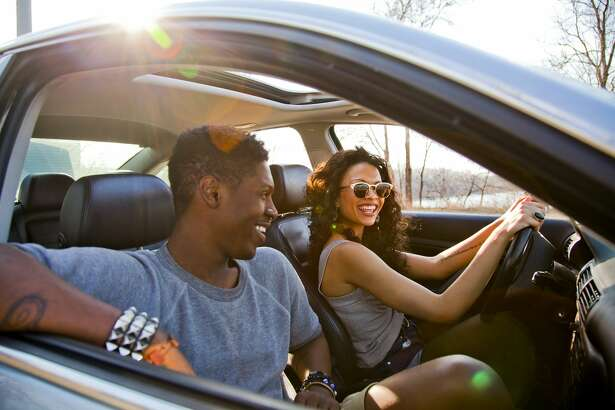 Smiling woman and man driving car