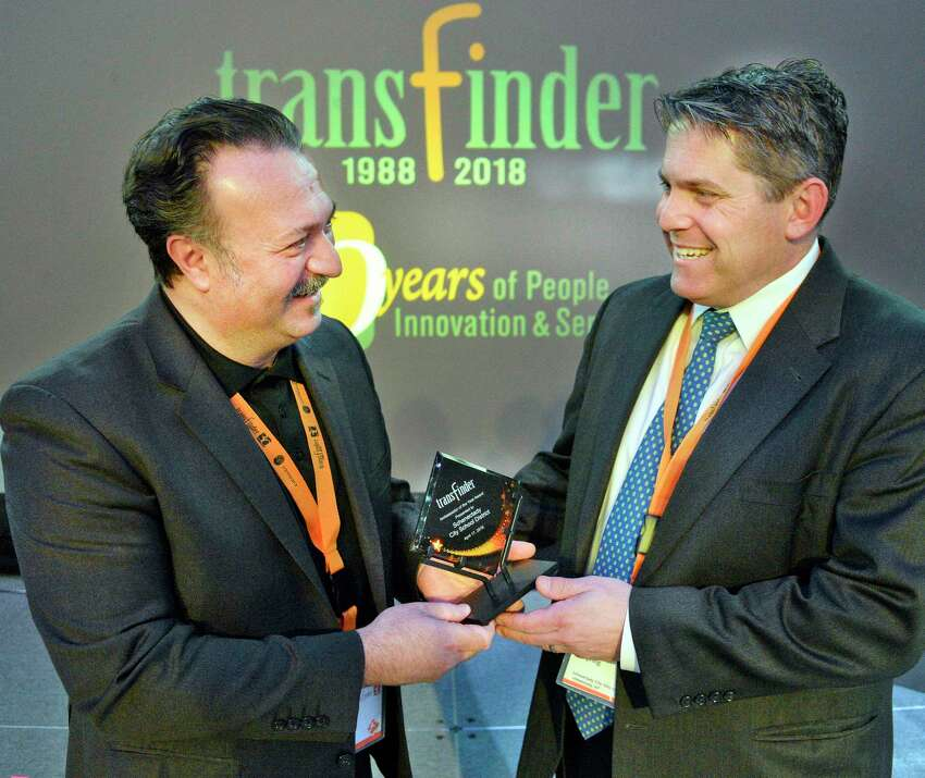 CEO Tony Civitella, left, presents their Ambassador of the Year Award to Schenectady Schools Superintendent Larry Spring during Transfinder's annual client conference at the Albany Capital Center Wednesday April 18, 2018 in Albany, NY. (John Carl D'Annibale/Times Union)