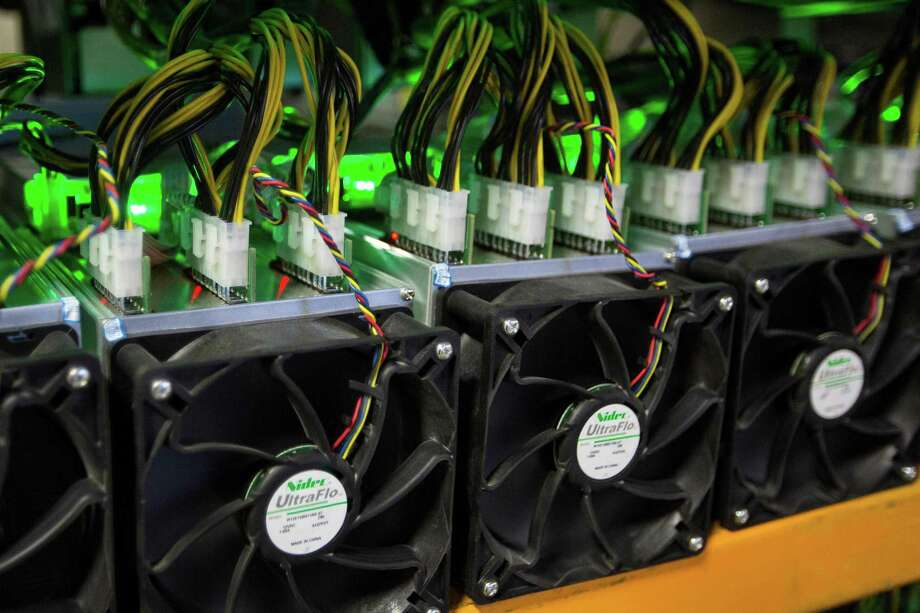 """(FILES) In this file photo taken on March 19, 2018 Bitcoin being mined at Bitfarms in Saint Hyacinthe, Quebec on March 19, 2018. At a former cocoa factory in Canada's Quebec province, tiny holes punctured in the walls allow fresh outside air to cool the thousands of whirring computer processors connected by a tangle of wires at Bitfarms, in a nondescript warehouse in Saint-Hyacinthe's industrial park, east of Montreal. / AFP PHOTO / Lars Hagberg / TO GO WITH AFP STORY by Clement Sabourin, """"Canada-cryptocurrency-computers-electricity""""LARS HAGBERG/AFP/Getty Images Photo: LARS HAGBERG / AFP/Getty Images / AFP or licensors"""