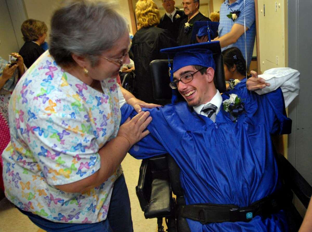 Langan School graduate David Nichols, right, joins primary care nurse Jane Gartley during commencement exercises on Tuesday, June 22, 2010, at the Center for Disability Services in Albany. (Cindy Schultz / Times Union)