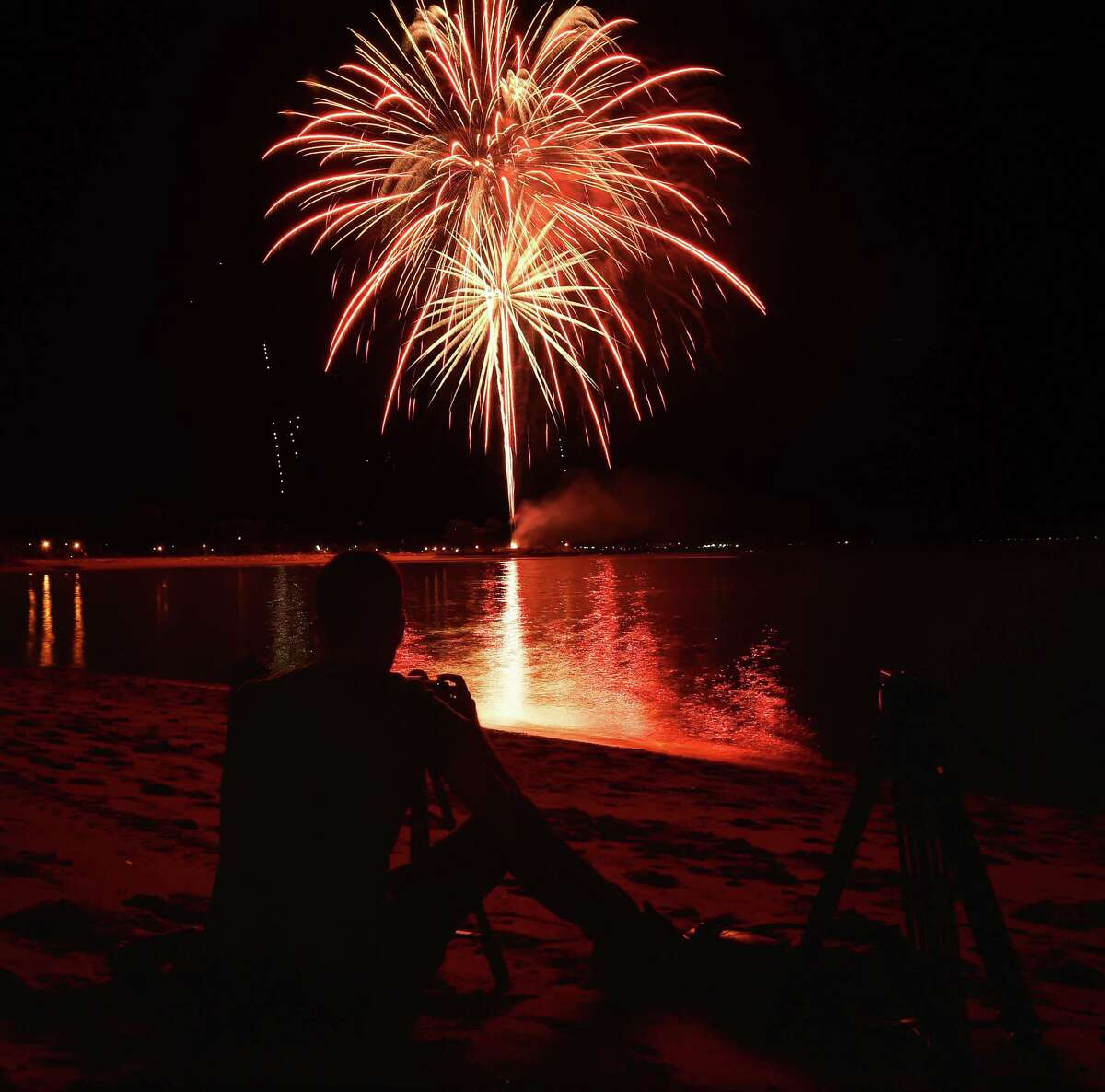 Milford resident Steven Cugini shoots stills and videos of the West Haven fireworks using a tripod on Gull Beach, Tuesday, July 5, 2016. The fireworks were postponed from last Friday, July 1, 2016, for inclement weather. (Catherine Avalone/New Haven Register / Hearst Connecticut Media