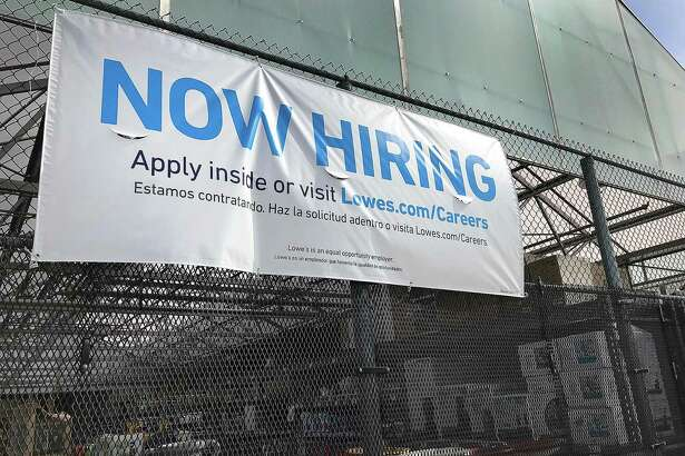 A sign notes that the Lowe's home improvement center in Danbury, Conn., is hiring during the spring of 2018.