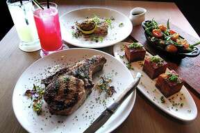 Food and drinks from Maverick Texas Brasserie. Clockwise from bottom left: double-cut pork chop, Bexar Chilcano cocktail, housemade ginger beer, six-ounce grilled red snapper fillet, blistered tomatoes and green beans side dish and a potato pave side dish.