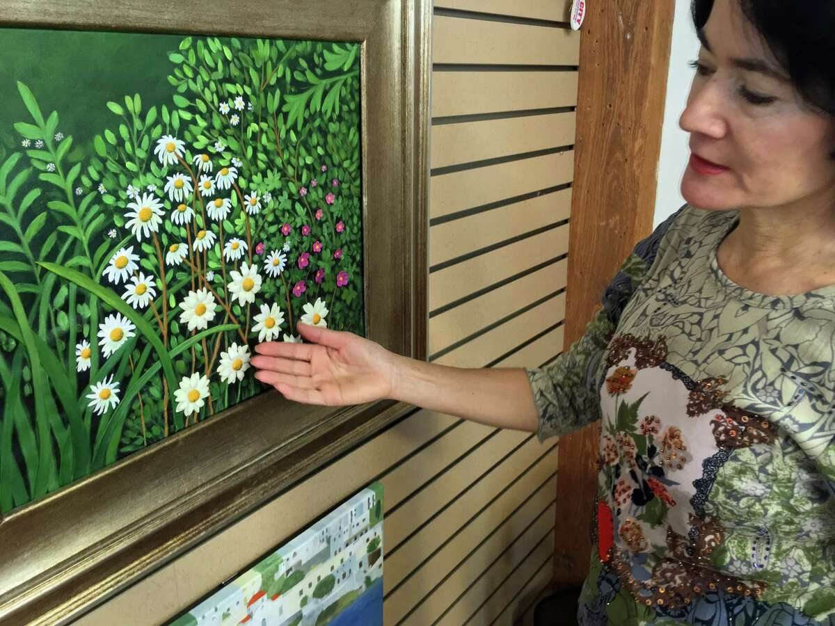Rosa Colon, a Stamford, Connecticut, artist, points out her porcelain work on canvas during a visit to her studio at the Loft Artists Association in Stamford on April 11, 2018.