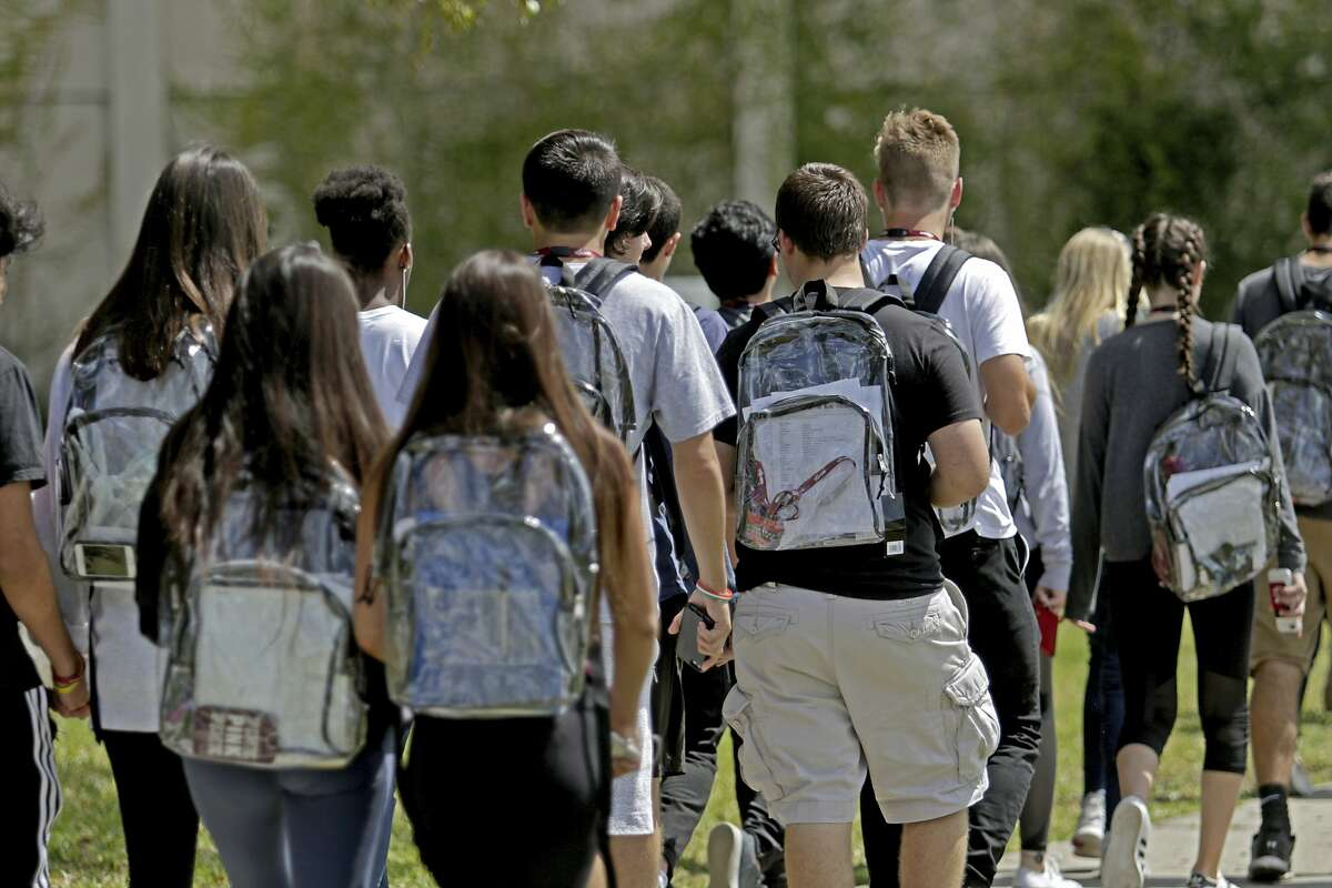 Students wear clear backpacks outside of Marjory Stoneman Douglas High School in Parkland, Fla., on Monday, April 2, 2018. The bags are one of a number of security measures the school district has enacted as a result of the Feb. 14 shooting at the school that killed 17.
