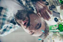 Close up portrait of dreamy drunk overdosed bearded guy surrounded by mess and dirt he was sniffing heroin on a table