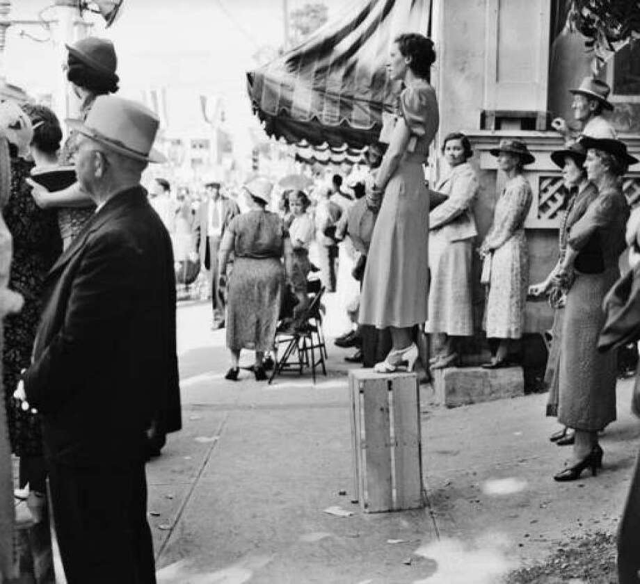 A woman identified as Mrs. Joe Lee shows impeccable balance, using a crate to get a better view of the 1937 Battle of Flowers Parade. Photo: Courtesy UTSA Special Collections