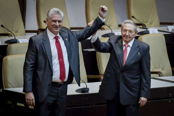 Cuba's new president Miguel Diaz-Canel, left, and former president Raul Castro, raise their arms after Diaz-Canel was elected as the island nation's new president, at the National Assembly in Havana, Cuba, Thursday, April 19, 2018. Castro left the presidency after 12 years in office when the National Assembly approved Diaz-Canel's nomination as the candidate for the top government position. (Adalberto Roque/Pool via AP)